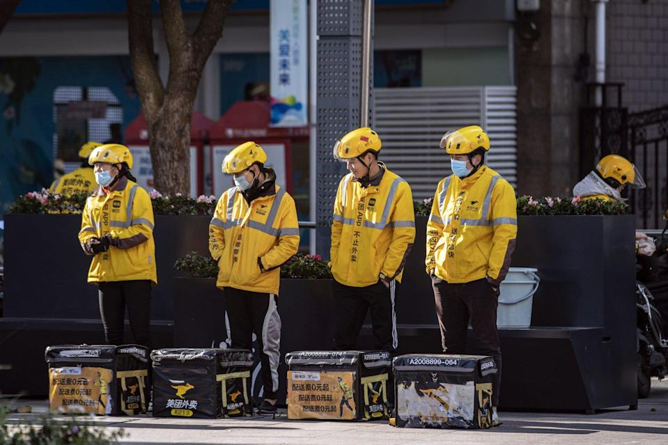 Food delivery couriers for Meituan stand with insulated bags during a morning briefing on a street in Shanghai. Photo: Bloomberg