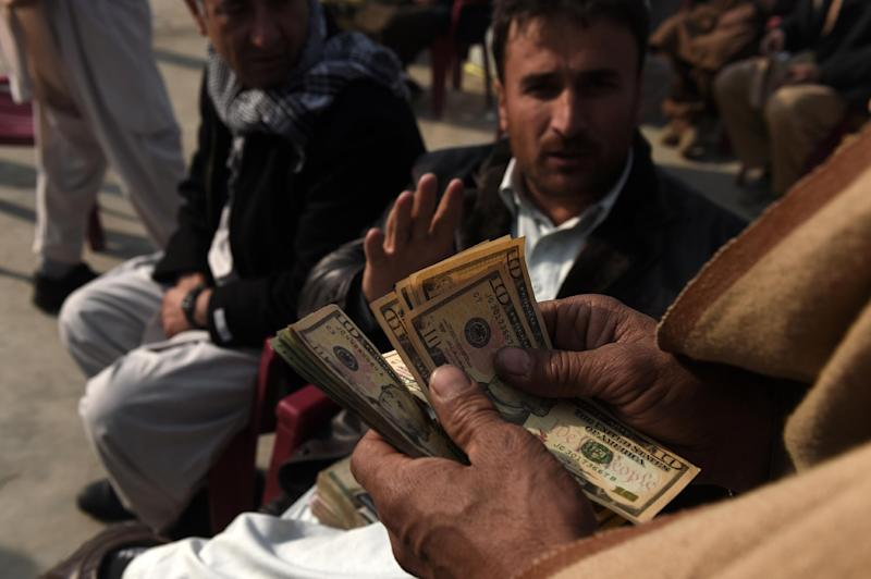 An Afghan Money Changer Counts Us Dollars At The Currency Exchange Sarayee Shahzada Market In Kabul