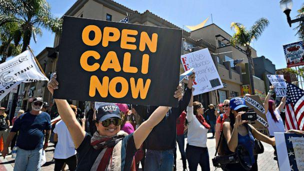PHOTO: Rose Riggio, from Los Angeles, joins a crowd of people gathered at the corner of Main Street and Walnut Avenue in Huntington Beach, Calif., to protest coronavirus (COVID-19) closures, April 17, 2020. (Jeff Gritchen/AP)