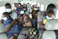 People fleeing fighting between insurgents and government forces in and around the northern Mozambican town of Palma are evacuated by plane to the Cabo Delgado provincial capital of Pemba, Mozambique, Thursday April 1, 2021. They were just a few of the thousands of residents who have fled to nearby Tanzania and south to the provincial capital of Pemba, according to international aid agencies. (Dave LePoidevin, MAF via AP)