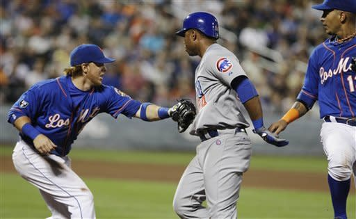 New York Mets second baseman Justin Turner, left, tags out Chicago Cubs' Luis Valbuena, center, as Mets' Ronny Cedeno watches during the fifth inning of a baseball game Friday, July 6, 2012, in New York. (AP Photo/Frank Franklin II)