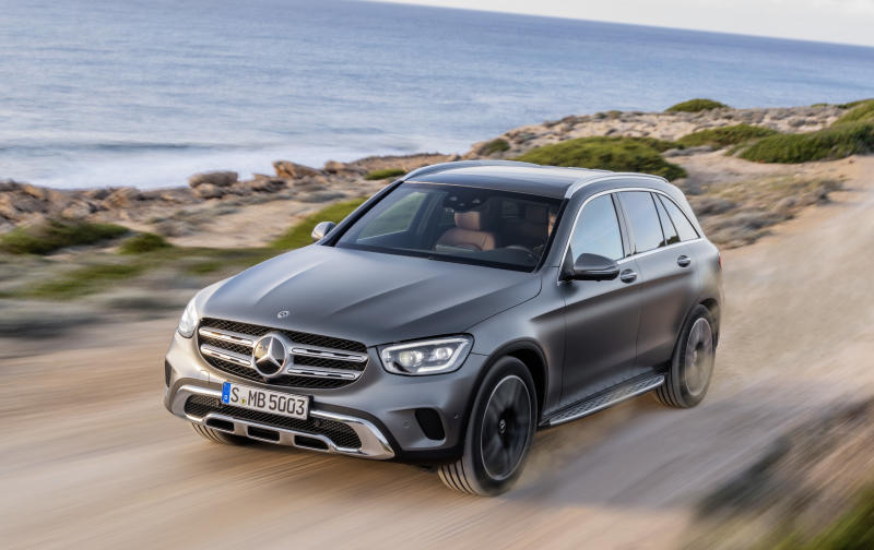 A dark gray 2019 Mercedes-Benz GLC, a small luxury crossover SUV, on a dirt road near a waterfront.