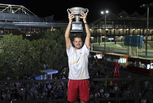 In this photo released by Tennis Australia, Stanislas Wawrinka of Switzerland holds his trophy aloft after defeating Spain's Rafael Nadal to win the men's singles title at the Australian Open tennis championship in Melbourne, Australia, Sunday, Jan. 26, 2014. (AP Photo/Tennis Australia,Fiona Hamilton)