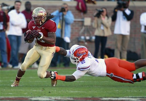Florida State running back Devonta Freeman runs past Florida defensive lineman Dominique Easley (2) during the first half of an NCAA college football game, Saturday, Nov. 24, 2012, in Tallahassee, Fla. (AP Photo/John Raoux)