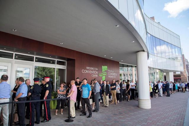 <p>Mourners line up to enter the Fredericton Convention Centre, where a public visitation for Fredericton police constables Sara Burns and Robb Costello is being held, in Fredericton on Thursday, Aug. 16, 2018. (Photo from The Canadian Press/Keith Minchin </p>