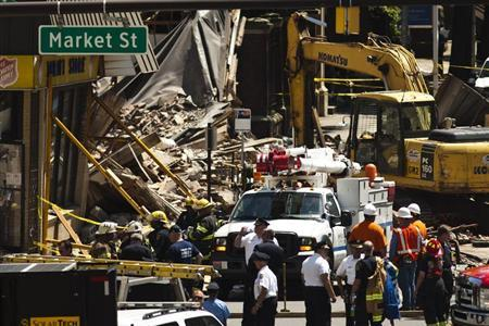Rescue workers search through rubble following a building collapse in Philadelphia