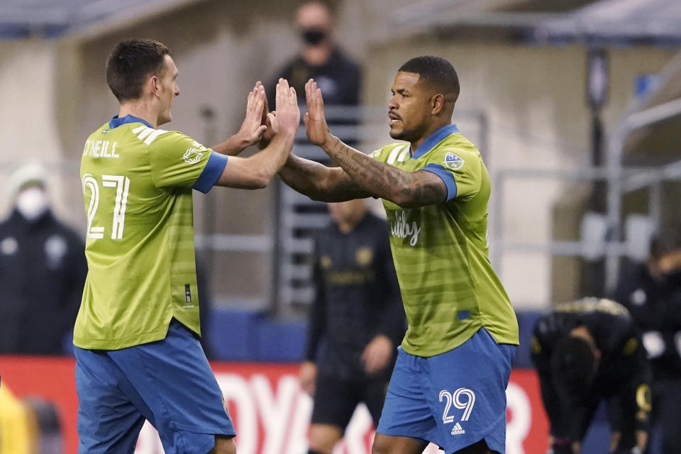 Seattle Sounders' Shane O'Neill (27) and Roman Torres (29) congratulate each other after the Sounders' 3-1 win over Los Angeles FC in an MLS playoff soccer match, Tuesday, Nov. 24, 2020, in Seattle. (AP Photo/Ted S. Warren)