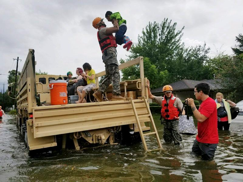 A photo made available by the Texas Military Department shows Texas National Guard soldiers arriving to aid citizens in heavily flooded areas in Houston.