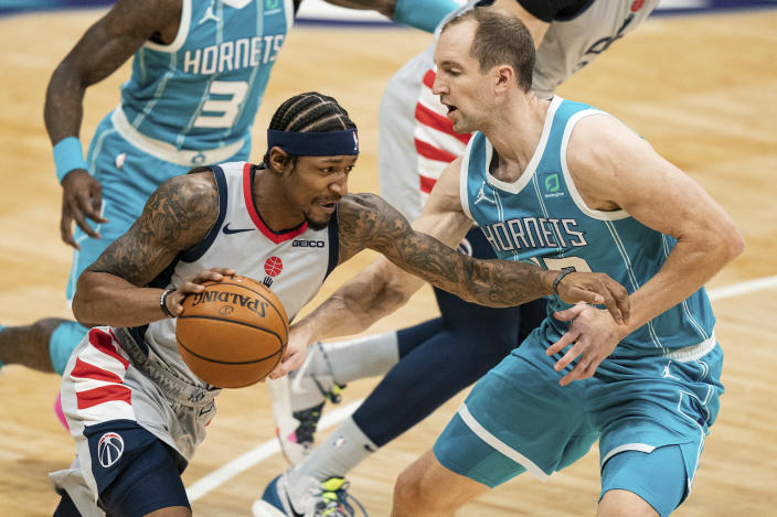 Washington Wizards guard Bradley Beal, front left, drives to the basket while guarded by Charlotte Hornets center Cody Zeller, right, during the first half of an NBA basketball game in Charlotte, N.C., Sunday, Feb. 7, 2021. (AP Photo/Jacob Kupferman)