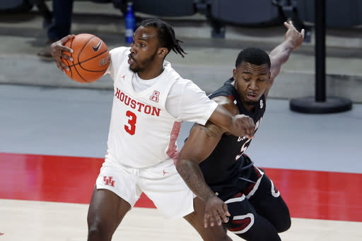 Houston guard DeJon Jarreau (3) spins away from the steal attempt by South Carolina guard Jermaine Couisnard (5), during the second half of an NCAA college basketball game Saturday, Dec. 5, 2020, in Houston. (AP Photo/Michael Wyke)