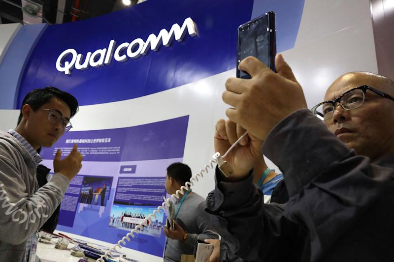 Attendees look at the latest technology from Qualcomm at the China International Import Expo in Shanghai, Tuesday, Nov. 6, 2018. Chinese President Xi Jinping has promised to open China's market wider as he opened a trade fair meant to promote the country's image as an importer, but he offered no response to U.S. and European complaints about technology policy and curbs on foreign business. (AP Photo/Ng Han Guan)