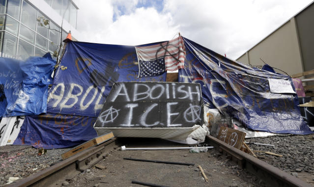 <p>A barricade crosses railroad track at a protest camp on property outside the U.S. Immigration and Customs Enforcement office in Portland, Ore., Monday, June 25, 2018. Law enforcement officers began distributing notices to vacate to demonstrators late Monday morning. The round-the-clock demonstration outside the Portland headquarters began June 17, 2018, and increased in size early last week, prompting officials to close the facility. (Photo: Don Ryan/AP) </p>