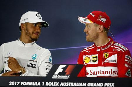 Formula One - F1 - Australian Grand Prix - Melbourne, Australia - 26/03/2017 - Ferrari driver Sebastian Vettel of Germany (R) speaks with second-placed Mercedes driver Lewis Hamilton of Britain at the post-race press conference. REUTERS/Brandon Malone