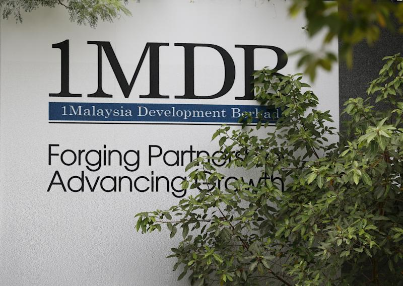 "Foliage partly covers a 1 Malaysia Development Berhad (1MDB) billboard at the funds flagship Tun Razak Exchange development in Kuala Lumpur, Malaysia, July 3, 2015. Malaysian Prime Minister Najib Razak slammed a report that said close to $700 million was wired to his personal account from banks, government agencies and companies linked to the debt-laden state fund 1MDB, claiming this was a ""continuation of political sabotage."" REUTERS/Olivia Harris"