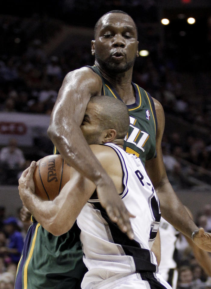 San Antonio Spurs' Tony Parker, front, of France, is fouled by Utah Jazz's Al Jefferson during the third quarter of Game 2 of a first-round NBA basketball playoff series, Wednesday, May 2, 2012, in San Antonio. (AP Photo/Eric Gay)