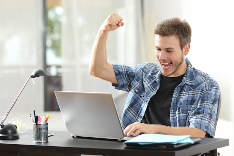 Man looking at laptop screen and raising his fist in celebration.