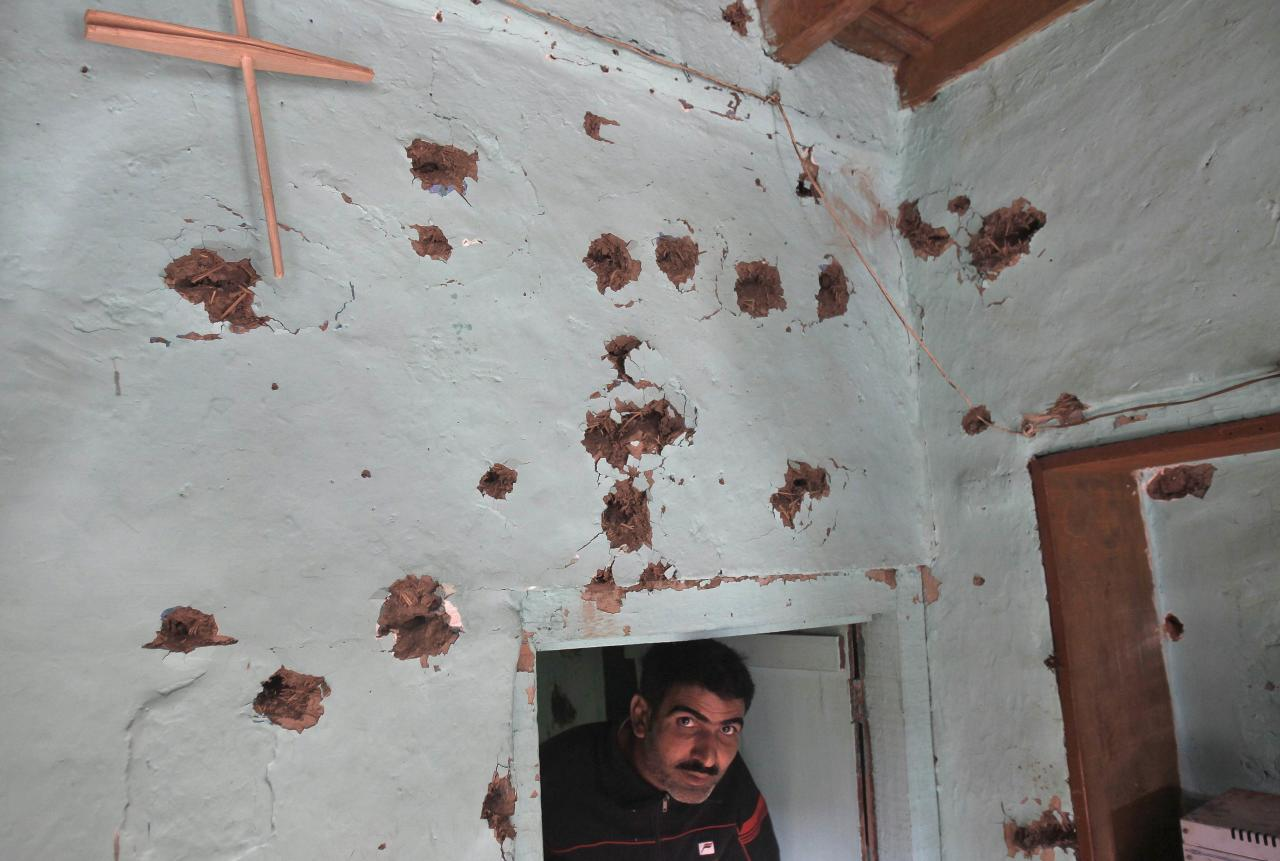 A Kashmiri man looks on under a bullet-ridden wall of a residential house after a gun battle on the outskirts of Srinagar, October 3, 2013. At least five Indian policemen were injured in the overnight gunfight between militants and security forces, police said on Thursday. REUTERS/Danish Ismail (INDIAN-ADMINISTERED KASHMIR - Tags: CIVIL UNREST SOCIETY)