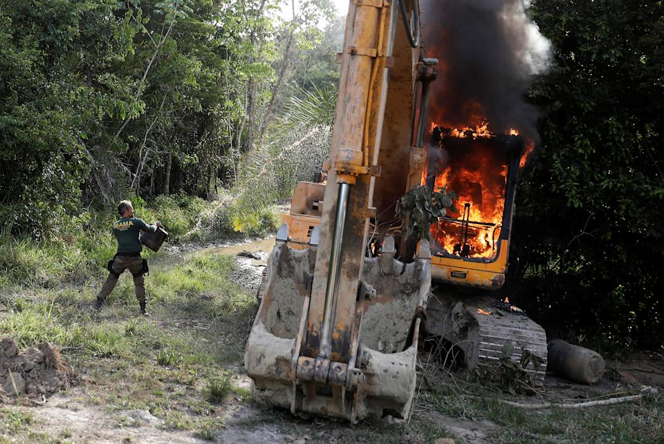 An agent of the Brazilian Institute for the Environment and Renewable Natural Resources (IBAMA) throws oil at a machine to destroy it at an illegal gold mine during an operation conducted jointly with the Federal Police near the city of Altamira, Para state, Brazil, August 30, 2019. REUTERS/Nacho Doce