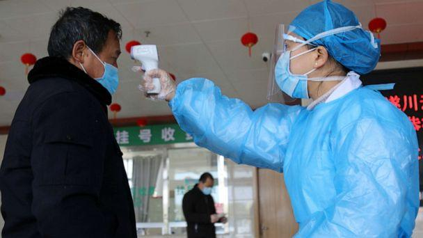 PHOTO: A medical worker takes a man's body temperature at an entrance to a hospital in Suichuan, Jiangxi province, China, on Feb. 2, 2020, as the country is hit by an outbreak of the new coronavirus. (China Daily/Reuters)