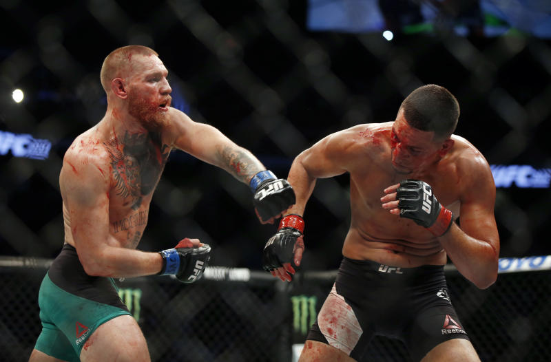 Conor McGregor fights Nate Diaz during their welterweight mixed martial arts bout at UFC 202 on Saturday, Aug. 20, 2016, in Las Vegas. McGregor won by split decision. (AP Photo/Isaac Brekken)