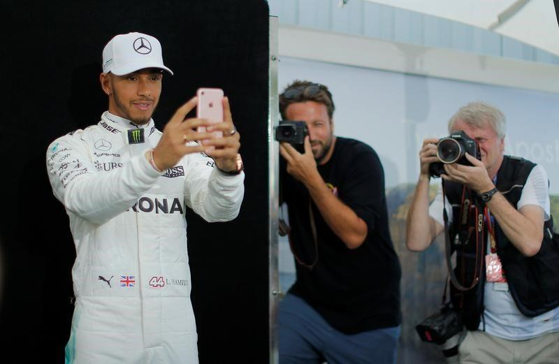 Mercedes driver Lewis Hamilton of Britain takes a selfie during the driver portrait session at the first race of the year - Credit: Reuters