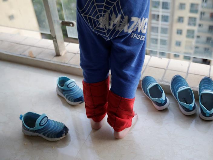 An Zhifei, one of An Hui's and Ye Jianbin's three sons, stands next to his and his brothers' shoes at home in Xishuangbanna, Yunnan province, China December 5, 2018. An and Ye are fathers of triplets who were conceived with the help of a German egg donor.