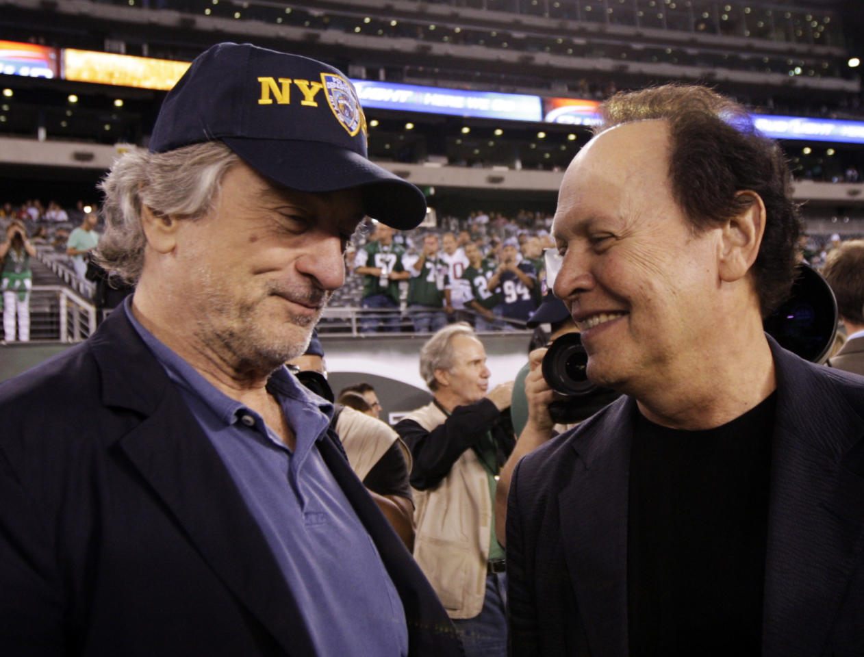 Actor Robert DeNiro, left, chats with actor Billy Crystal before an NFL football game between the Dallas Cowboys and the New York Jets Sunday, Sept. 11, 2011, in East Rutherford, N.J. (AP Photo/Julio Cortez)