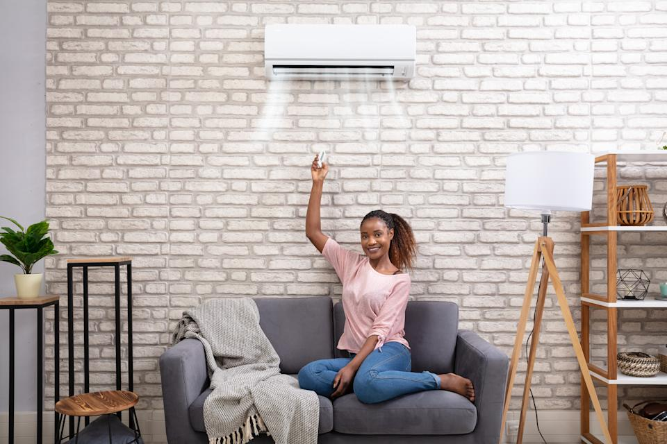 Young African Woman Switching On Air Conditioner With Remote Control At Home
