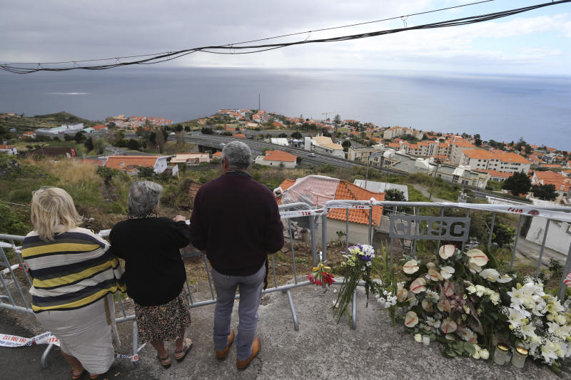 People stand by flowers placed at the spot where a tourist bus veered off the road crashing into a house, seen below, killing 29 people in Funchal, the capital of Portugal's Madeira Island, Friday April 19, 2019. A German plane is expected to arrive Friday in Madeira to take home survivors from the bus accident that killed 29 tourists after it veered off the road and plunged down a slope. All the deceased were German. The bus carried 55 people, including a Portuguese driver and guide. Sixteen people remain hospitalized, but authorities said all of them are out of danger. (AP Photo/Armando Franca)