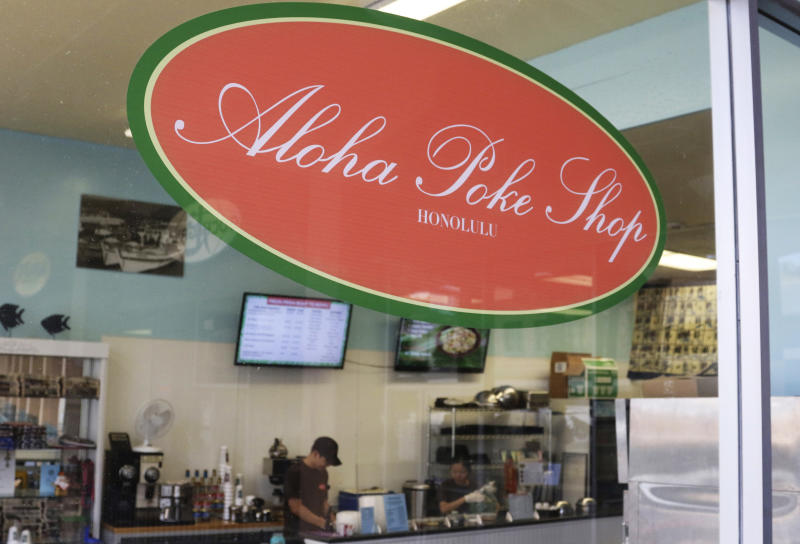 "This Tuesday, April 16, 2019, photo shows Aloha Poke Shop, a store in Honolulu that received a letter from Chicago-based Aloha Poke Co. saying the Illinois company had trademarked ""Aloha Poke"" and the Hawaii company would need to change its name. Hawaii lawmakers are considering adopting a resolution calling for the creation of legal protections for Native Hawaiian cultural intellectual property. (AP Photo/Audrey McAvoy)"