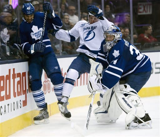Toronto Maple Leafs goaltender James Reimer clears the puck as defenceman Mark Fraser, left, holds off Tampa Bay Lightning left winger Ondrej Palat during the first period of an NHL hockey game in Toronto on Wednesday, March 20, 2013. (AP Photo/The Canadian Press, Frank Gunn)