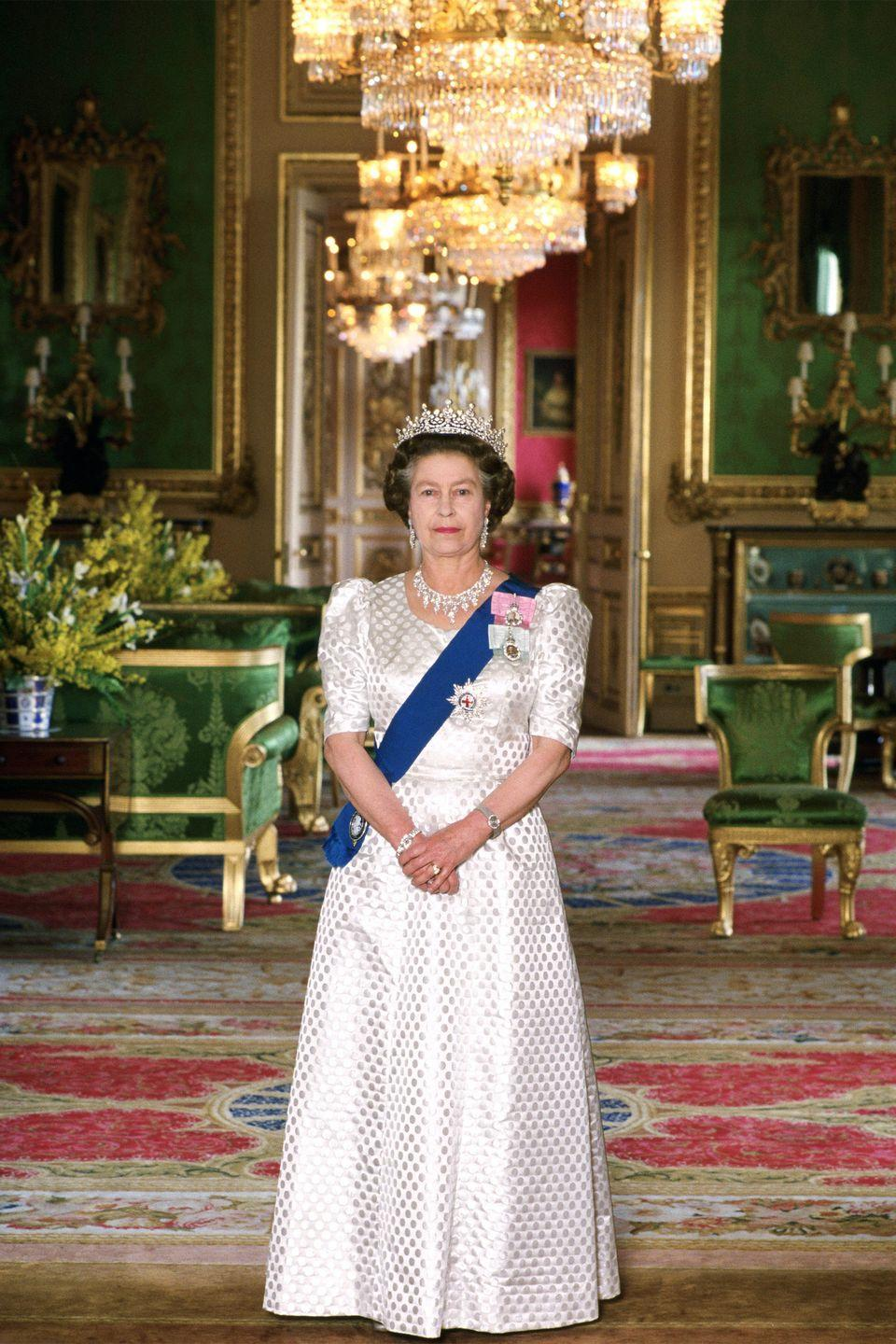 <p>The queen is photographed in the Green Room at Windsor Castle in a printed gown, diamond chandelier earrings, a silver watch, a diamond necklace, diamond bracelets, and a tiara.</p>
