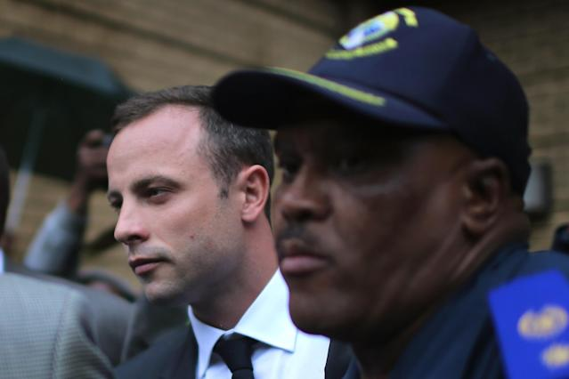 PRETORIA, SOUTH AFRICA - MARCH 03: Oscar Pistorius (L) is escorted by police as he leaves North Gauteng High Court at the end of the first day of his trial accused of the murder of his girlfriend Reeva Steenkamp on March 3, 2014 in Pretoria, South Africa. Olympic and Paralympic athlete Oscar Pistorius, aged 27, is accused of murdering his girlfriend Reeva Steenkamp. Pistorius denies the allegation claiming he mistook Steenkamp for an intruder inside their home on Valentines Day 2013. (Photo by Christopher Furlong/Getty Images)
