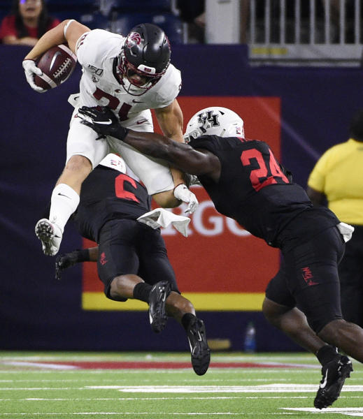 Washington State running back Max Borghi, top left, leaps over Houston cornerback Damarion Williams, bottom, as linebacker Donavan Mutin makes the tackle during the second half of an NCAA college football game Friday, Sept. 13, 2019, in Houston. (AP Photo/Eric Christian Smith)