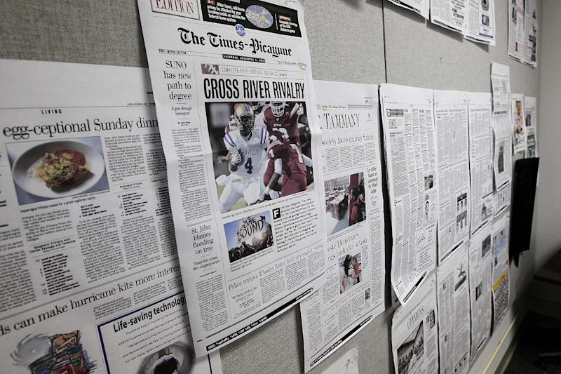 Prototypes of the future three-day-a-week New Orleans Times-Picayune are seen taped to a door in a workroom in their news offices in New Orleans, Thursday, Sept. 27, 2012. As The Times-Picayune in New Orleans scales back its print edition to three days a week, the Baton Rouge newspaper is starting its own daily edition to try to fill the void. The move by The Advocate sets up an old-fashioned newspaper competition, even as more and more people get their news online and from cellphones.(AP Photo/Gerald Herbert)