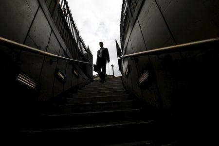 A man walks down steps into Bank tube station in the City of London, in this July 23, 2010 file photo. REUTERS/Andrew Winning/Files