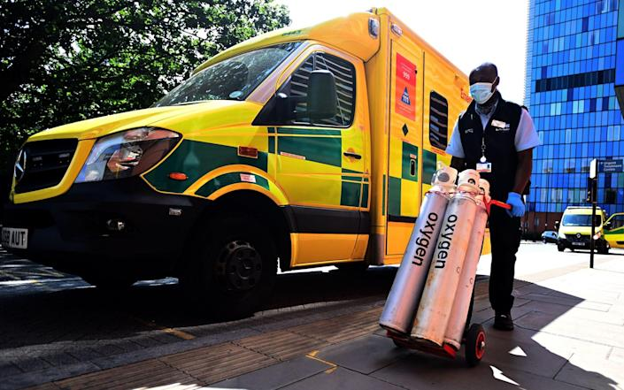 A hospital worker moves oxygen tanks outside the Royal London hospital, as Covid-19 cases continue to rise, on 23 July 2021 - Andy Rain/Shutterstock