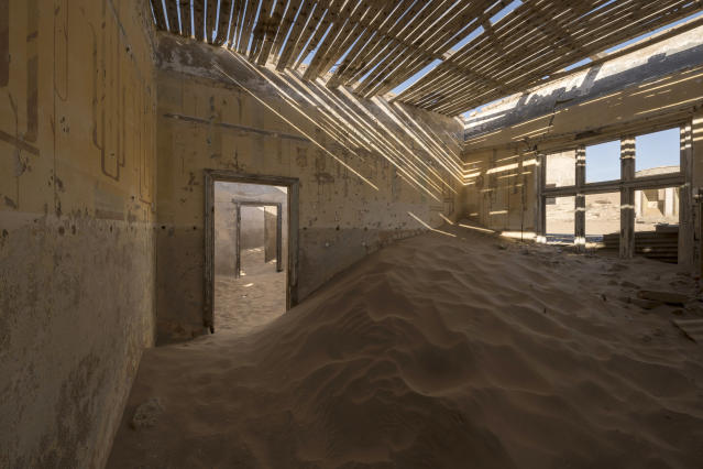 <p>The town was ultimately abandoned in 1954. The geological forces of the desert mean that tourists now walk through houses knee-deep in sand. (Photo: David Swindler/Caters News) </p>