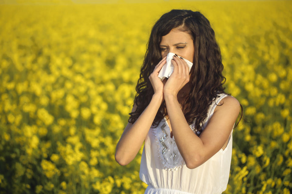 Young woman with pollen allergy, blowing her nose in a handkerchie. About 25 years, Caucasian female.
