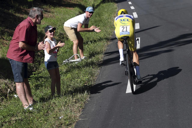 Spectators cheers France's Julian Alaphilippe wearing the overall leader's yellow jersey as he rides during the thirteenth stage of the Tour de France cycling race, an individual time trial over 27.2 kilometers (16.9 miles) with start and finish in Pau, France, Friday, July 19, 2019. (AP Photo/Thibault Camus)