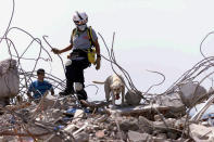 """FILE - In this Aug. 23, 1999, file photo, Elena Lopez, of the Miami-Dade Fire Rescue, Florida Task Force One, Urban Search and Rescue team, searches the rubble in Izmit, Turkey, with her search dog """"Thea."""" Search and rescue teams from Miami-Dade have been described as among the best and most experienced in the world. (Patrick Farrell/Miami Herald via AP, File)"""