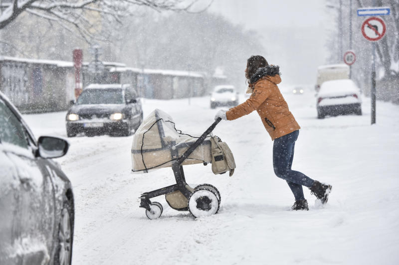 A woman pushes a pram across the street during heavy snowfall in Bratislava, Slovakia, Tuesday, Jan. 8, 2019. Cold weather has engulfed many parts of Europe Tuesday. (Pavol Zachar/TASR via AP)