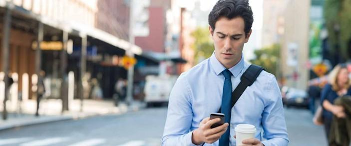 Businessman using smartphone and holding paper cup ina urban scene. Worried businessman walking on the road and messaging with phone.