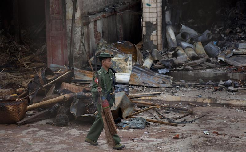 An army officer walks with brooms in front of a burned building that housed an orphanage for Muslim children in Lashio, northern Shan State, Myanmar, Thursday, May 30, 2013. Many Buddhists and Muslims stayed locked inside their homes and shops were shuttered after two-days of violence in Lashio town, near the border with China, the latest region to fall prey to the country's spreading sectarian violence.(AP Photo/Gemunu Amarasinghe)