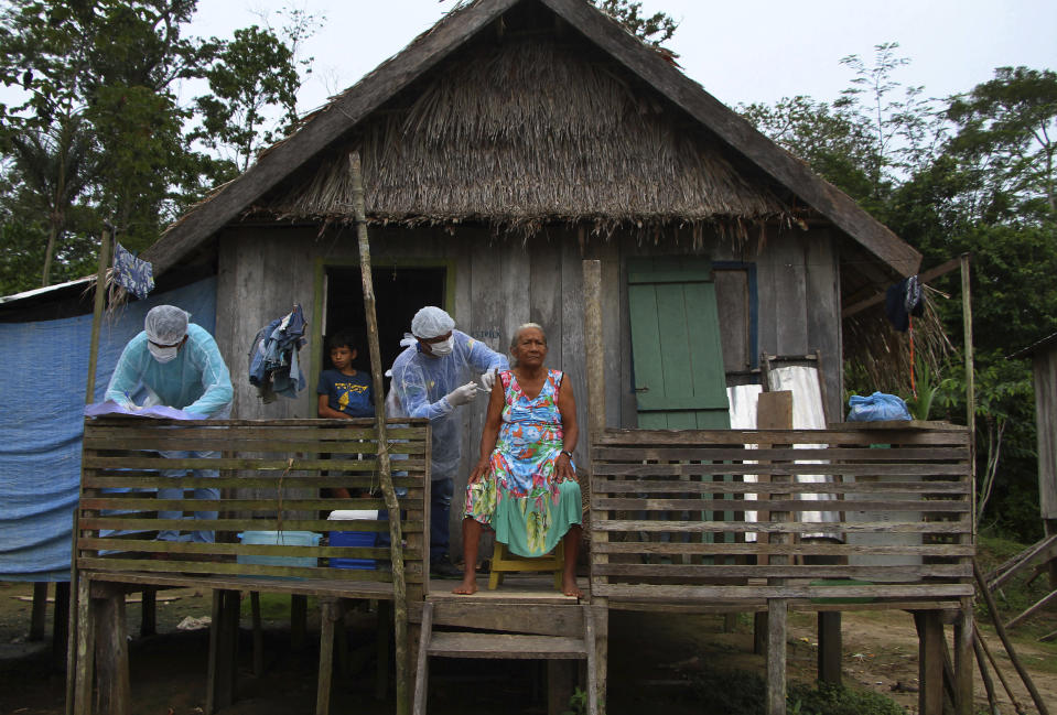 Maria Castro de Lima, 72, receives a dose of the Oxford-AstraZeneca COVID-19 vaccine from a healthcare worker, while sitting on the porch of her home in the Recanto community, along the Purus River, in the Labrea municipality, Amazonas state, Brazil, Friday, Feb. 12, 2021. (AP Photo/Edmar Barros)