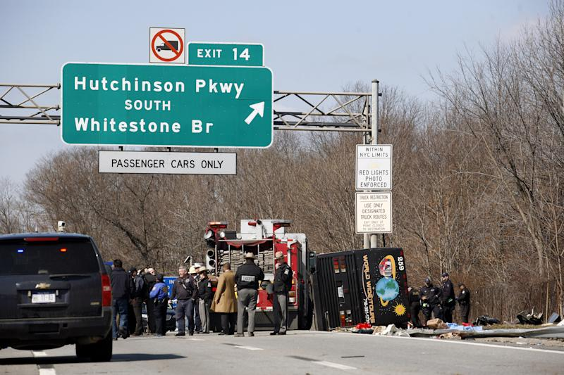FILE - In this March 12, 2011 file photo, Emergency personnel investigate the scene of a bus crash on Interstate-95 in the Bronx borough of New York. Twenty-six bus operations that transported more than 1,800 passengers a day along Interstate 95 between New York and Florida have been closed for safety violations in what federal officials say is the government's largest single safety crackdown of the motor coach industry in at least a decade.  (AP Photo/David Karp, File)