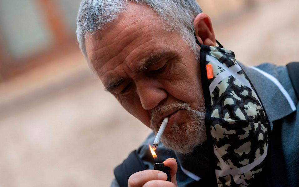 Smokers are prohibited from lighting up outdoors unless they can be sure to maintain a safe social distance - Jose Jordan/AFP