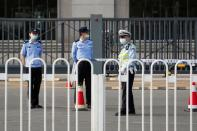 Police officers stand guard outside Beijing No. 2 Intermediate People's Court where Australian writer Yang Hengjun is expected to face trial on espionage charges, in Beijing