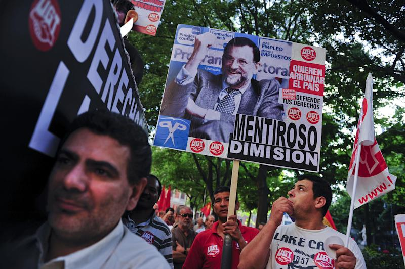 Demonstrators calling to general strike while they protest against cutback plans by Spain's government holding a banner against Spanish Prime Minister, Mariano Rajoy reading '' Liar. Resignation '', in Pamplona, northern Spain, Thursday, July 19, 2012. (AP Photo/Alvaro Barrientos)