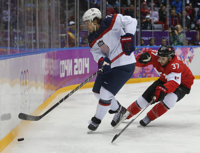 Canada forward Patrice Bergeron, right, challenges USA defenseman Justin Faulk for the puck during the first period of a men's semifinal ice hockey game at the 2014 Winter Olympics, Friday, Feb. 21, 2014, in Sochi, Russia. (AP Photo/Petr David Josek)